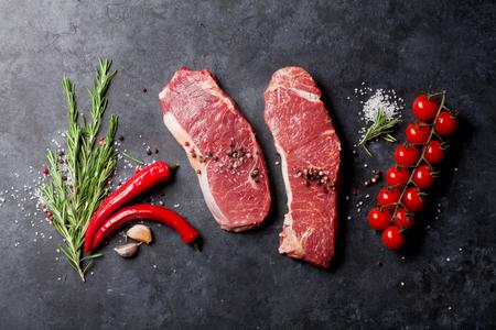 carne cruda: Lomo de filete sin procesar con romero, sal y pimienta cocinar sobre mesa de piedra. Vista superior