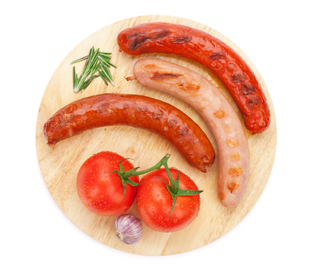 embutidos: Varias salchichas a la parrilla con los condimentos y los tomates en la tabla de cortar. Aislado en el fondo blanco Foto de archivo