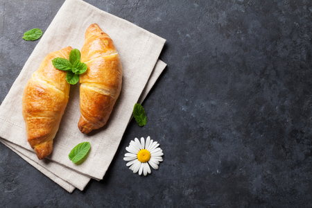 Fresh croissants and chamomile flowers on stone table. Morning background. Top view with copy space
