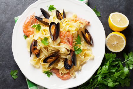 plates of food: Pasta with seafood on stone table. Mussels and prawns. Top view