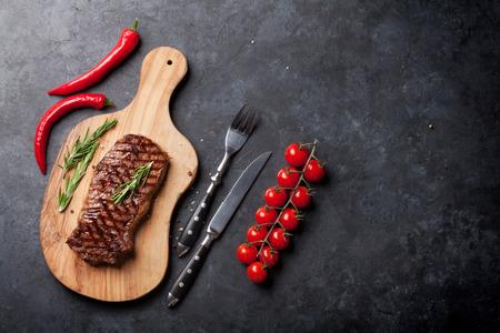 Filete de carne a la parrilla en la tabla de cortar sobre la mesa de piedra. Vista superior con espacio de copia Foto de archivo - 58503035