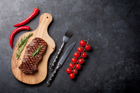 Grilled beef steak on cutting board over stone table. Top view with copy space Stok Fotoğraf - 58503035
