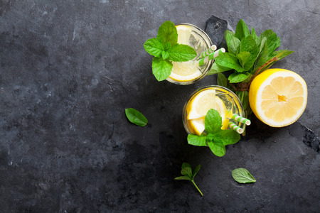 vasos de agua: Lemonade with lemon, mint and ice on stone table. Top view with copy space