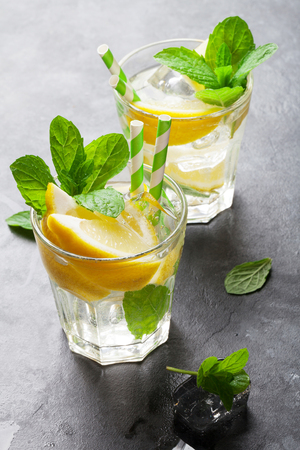 summer fruit: Lemonade with lemon, mint and ice on stone table