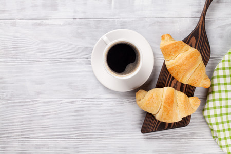 coffee table: Fresh croissants and coffee on wooden table. Top view with copy space