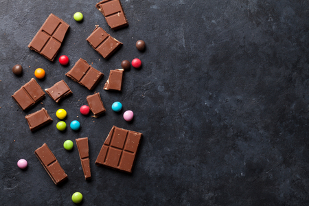 Chocolate and candy sweets on dark stone background. Top view with copy space Stock Photo