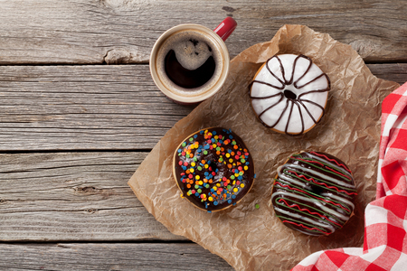 sweet bun: Donuts and coffee on wooden table. Top view with copy space