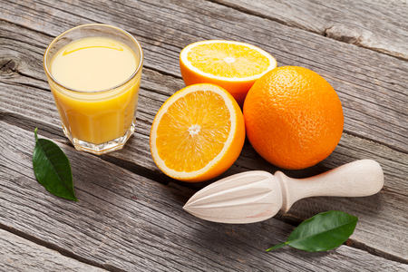 wood board: Fresh ripe oranges and juice on wooden table