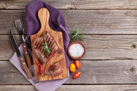 로즈마리, 소금과 후추 나무 테이블에 구운 된 쇠고기 스테이크. 복사 공간이있는 상위 뷰