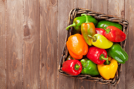 Fresh colorful bell pepper box on wooden table. Top view with copy space