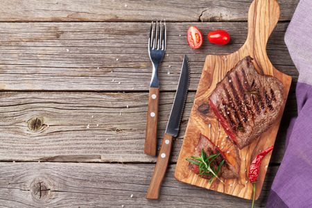 roast: Grilled beef steak with rosemary, salt and pepper on wooden table. Top view with copy space