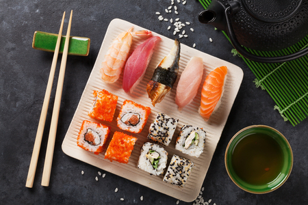 nigiri: Set of sushi, maki and green tea on stone table. Top view