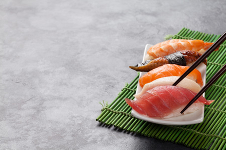 De reeks van sushi en eetstokjes op stenen tafel. Weergave met kopie ruimte Stockfoto