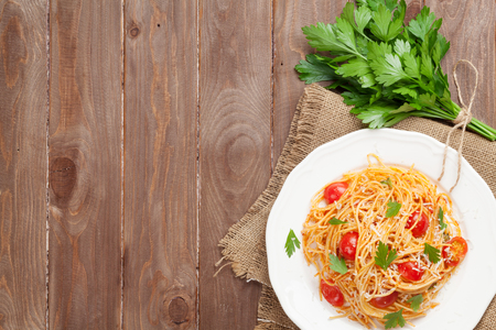 Spaghetti pasta with tomatoes and parsley on wooden table. Top view with copy space Imagens