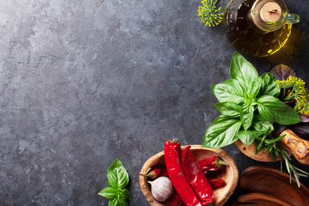 Fresh garden herbs in mortar, chili pepper and olive oil on stone table. Basil, rosemary, dill. Cooking ingredients. Top view with copy space