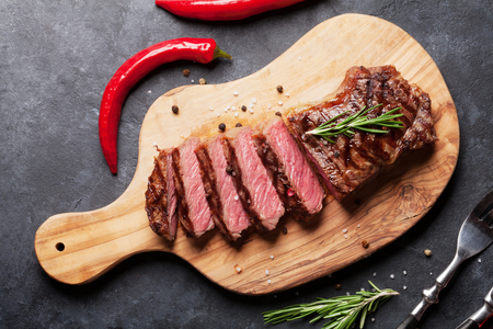 Grilled sliced beef steak on cutting board over stone table. Top view Standard-Bild