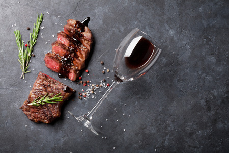 Grilled sliced beef steak with balsamico and rosemary and red wine on stone table. Top view with copy space