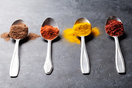 indian mustard: Colorful spices in spoons over stone table