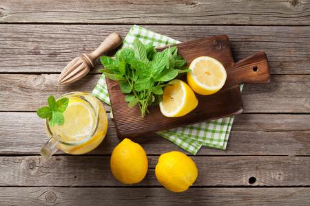 レモン、ミントの庭のテーブルに氷とレモネード ピッチャー。トップ ビュー 写真素材