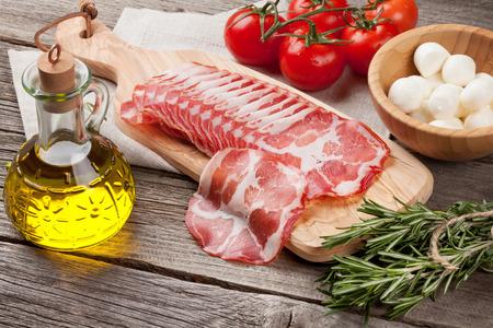 sliced cheese: Prosciutto and mozzarella on wooden table Stock Photo