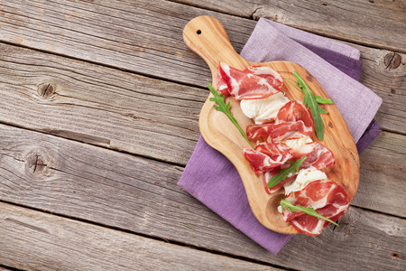 appetizers: Prosciutto and mozzarella on wooden table. Top view with copy space Stock Photo