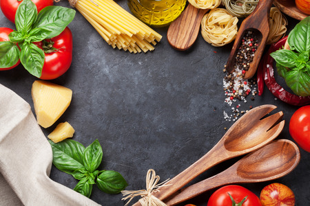 ingredient: Italian food cooking. Tomatoes, basil, spaghetti pasta, olive oil and chili pepper on stone kitchen table. Top view with copy space for your recipe