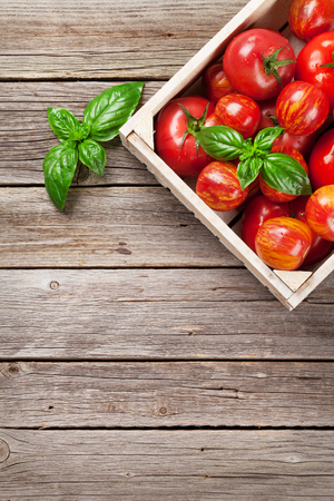 herbs boxes: Fresh ripe garden tomatoes and basil on wooden table. Top view with copy space