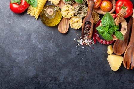 Italian food cooking. Tomatoes, basil, spaghetti pasta, olive oil and chili pepper on stone kitchen table. Top view with copy space for your recipe