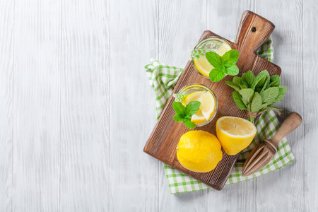 cutting board: Lemonade with lemon, mint and ice on wooden table. Top view with copy space
