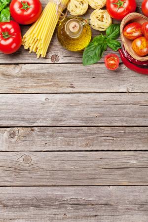 Italienisches Essen kochen. Tomaten, Basilikum, Spaghetti Pasta, Olivenöl und Chili-Pfeffer auf hölzernen Küchentisch. Ansicht von oben mit Kopie Raum