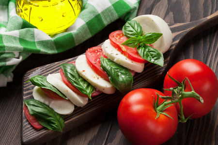 basil herb: Caprese salad. Mozzarella cheese, tomatoes and basil herb leaves on cutting board over wooden table Stock Photo