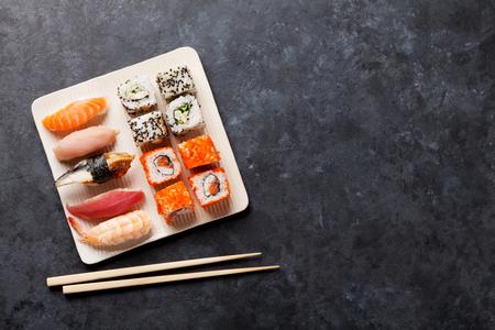寿司とマキのセットは、石のテーブルのロールします。コピー スペース平面図