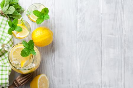 vaso de jugo: Limonada con limón, menta y hielo en la mesa de madera. Vista superior con espacio de copia Foto de archivo