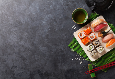 table set: Set of sushi, maki and green tea on stone table. Top view with copy space