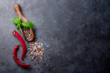 Pfeffer und Salz Gewürze, Basilikum Kräuter und Chili-Pfeffer. Rot, weiß und schwarz Peppercorn. Auf dunklen Steintisch. Ansicht von oben mit Kopie Raum