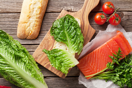 romaine: Sandwich cooking with ciabatta bread, salmon and romaine salad on wooden table. Top view