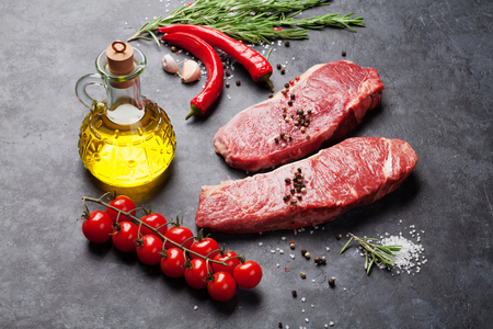 Raw Meat: Raw striploin steak with rosemary, salt and pepper cooking over stone table