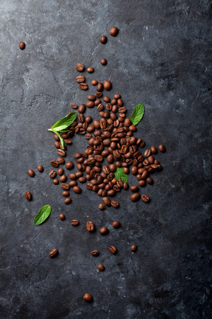 Coffee beans and mint leaves on dark stone table. Top view