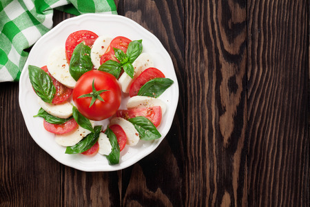 basil herb: Caprese salad. Mozzarella cheese, tomatoes and basil herb leaves on plate over wooden table. Top view with copy space