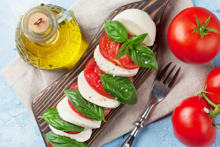 basil herb: Caprese salad. Mozzarella cheese, tomatoes and basil herb leaves on cutting board over stone table. Top view
