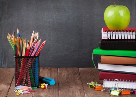 utiles escolares: útiles escolares y de oficina y la manzana en la tabla de aula en frente de la pizarra. Ver con espacio de copia