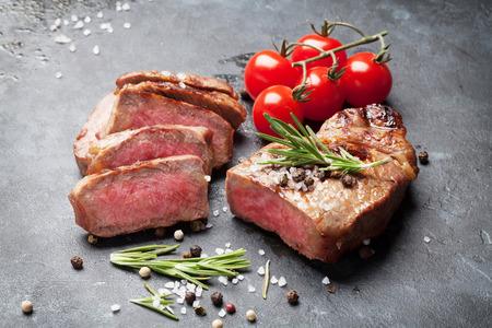 carne asada: La parrilla filete de carne en rodajas con sal, pimienta y romero en la mesa de piedra