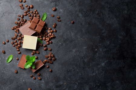 Chocolate and coffee beans on dark stone table. Top view with copy space