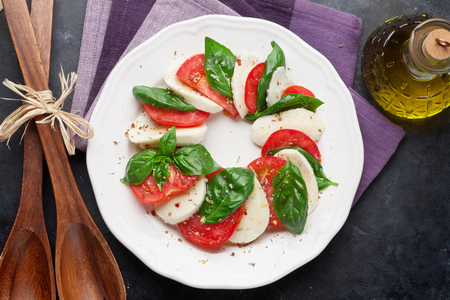 basil herb: Caprese salad. Mozzarella cheese, tomatoes and basil herb leaves on plate over stone table. Top view