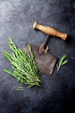 stone cutter: Rosemary bunch. Herbs and spices cooking on stone table. Top view
