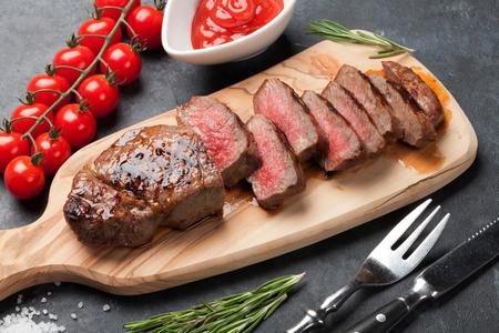 돌 테이블에 걸쳐 커팅 보드에 구운 슬라이스 쇠고기 스테이크