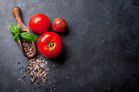 red pepper: Pepper and salt spices, basil herb and tomatoes. Red, white and black peppercorn. On dark stone table. Top view with copy space Stock Photo