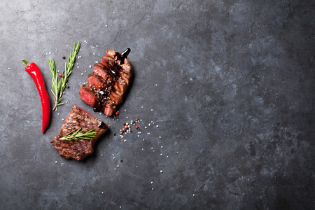rare background: Grilled sliced beef steak with balsamico and rosemary on stone table. Top view with copy space