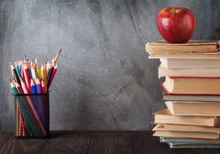 Libri e rifornimenti davanti alla lavagna. Torna al concetto di scuola con spazio di copia