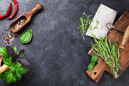 wood cutter: Herbs and spices cooking on stone table. Basil, rosemary, pepper and salt. Top view with copyspace